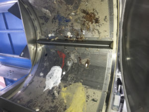 Industrial dryer heavily contaminated with foreign objects.